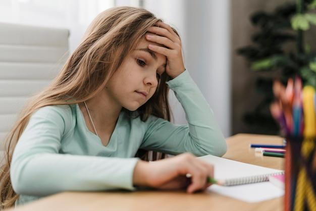 Meisje met hoofdpijn tijdens het doen van online lessen