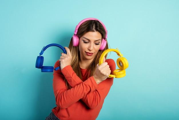 Meisje met hoofdtelefoon luistert naar muziek en dansen. emotionele en energetische expressie. cyaan achtergrond