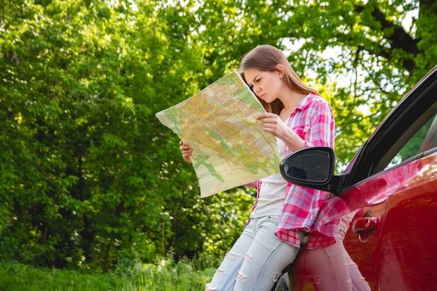 Meisje met in hand kaart die zich naast een auto in het bos bevindt.