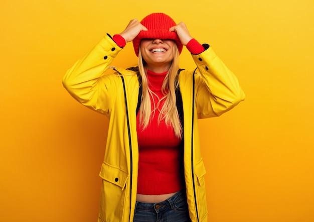 Meisje met jasje op gele achtergrond bedekt haar gezicht met haar hoed voor het regenachtige weer