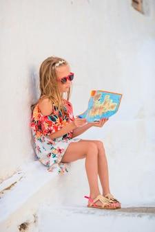 Meisje met kaart van eiland in openlucht in oude straten mykonos. jong geitje bij straat van typisch grieks traditioneel dorp met witte muren en kleurrijke deuren op mykonos-eiland, in griekenland