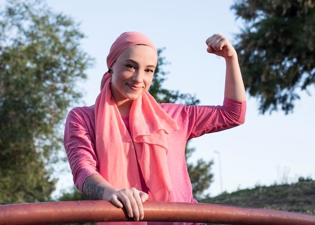 Meisje met kanker roze sjaal, overleven kanker met opgeheven vuist
