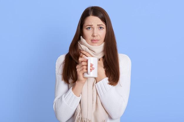 Meisje met keelpijn en hete thee drinken
