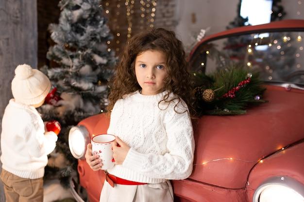 Meisje met kerst kopje tee in de buurt van rode auto en kerstbomen met verlichting
