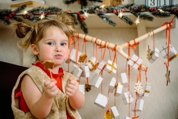 Meisje met kerst peperkoek en geschenken opknoping op een tak