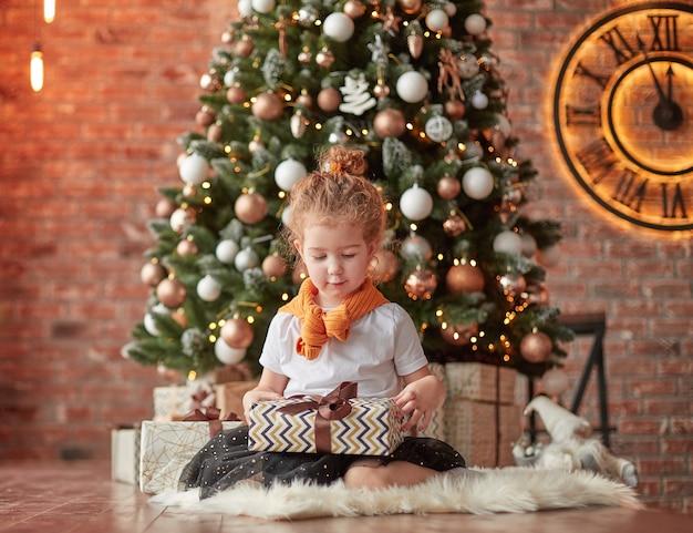 Meisje met kerstcadeaus zitten in de buurt van de kerstboom