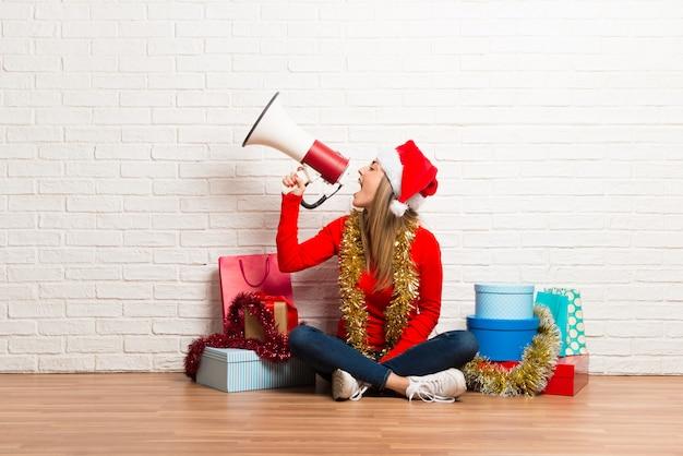 Meisje met kerstmishoed en vele giften die de kerstmisvakantie vieren die een megafoon houden