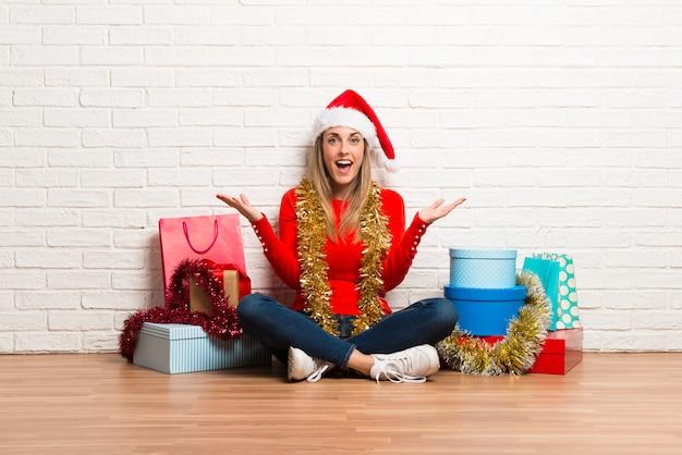 Meisje met kerstmishoed en vele giften die de kerstmisvakantie vieren