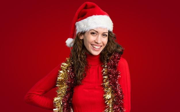 Meisje met kerstmishoed over geïsoleerde rode muur