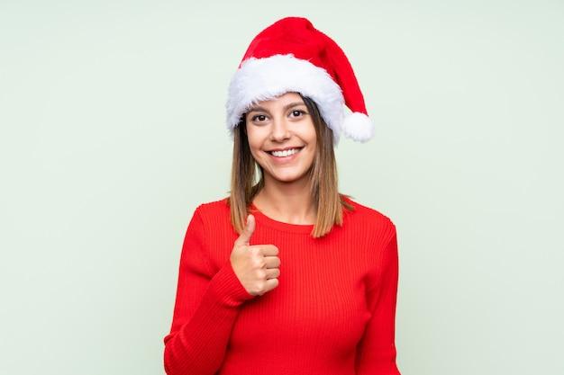 Meisje met kerstmishoed over het geïsoleerde groene geven duimen op gebaar