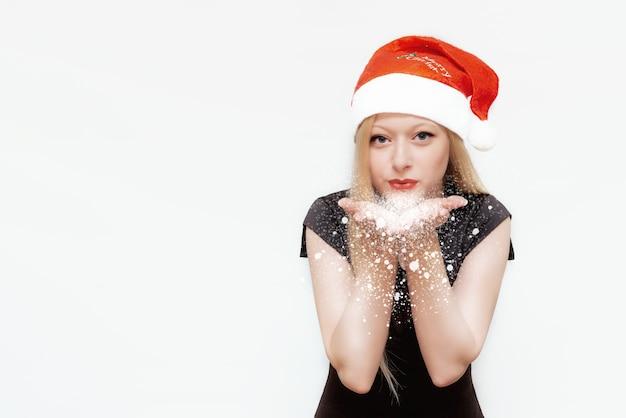 Meisje met kerstmuts blaast sneeuw uit haar handpalmen