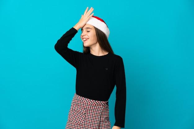 Meisje met kerstmuts geïsoleerd op blauwe achtergrond heeft iets gerealiseerd en de oplossing voornemens