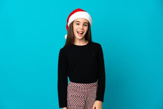Meisje met kerstmuts geïsoleerd op blauwe achtergrond met verrassingsgelaatsuitdrukking