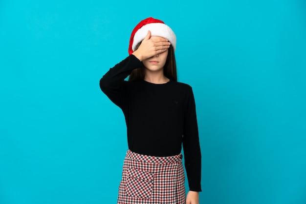 Meisje met kerstmuts geïsoleerd op blauwe muur die ogen behandelt door handen. ik wil niets zien