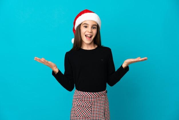 Meisje met kerstmuts geïsoleerd op blauwe muur met geschokt gelaatsuitdrukking