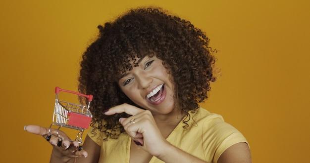 Meisje met kleine boodschappenkaart. glimlachende en dansende vrouw met krullend haar in winkelconcept. jonge vrouw met een miniatuurkar. e-commerce en zaken. winkelen auto. vrouw shopper. gele achtergrond.