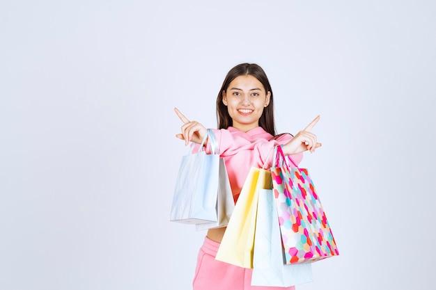 Meisje met kleurrijke boodschappentassen die naar links en rechts wijzen.