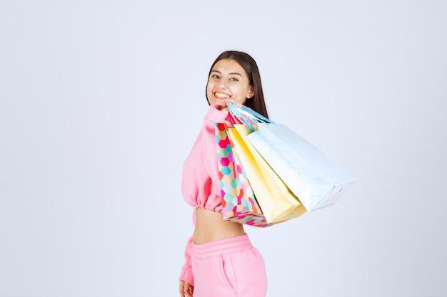 Meisje met kleurrijke boodschappentassen terug op haar schouder.