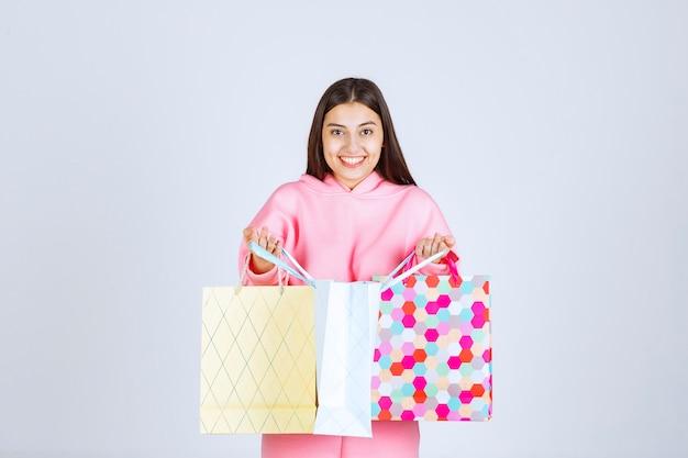 Meisje met kleurrijke boodschappentassen ze te openen en te controleren.