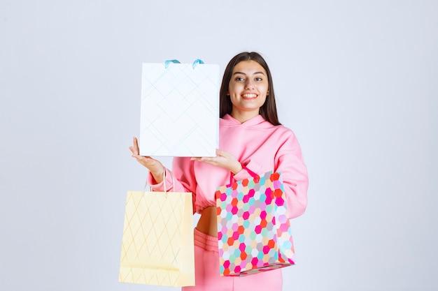 Meisje met kleurrijke boodschappentassen ziet er blij en tevreden uit.