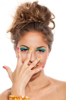 Meisje met kleurrijke manicure en make-up