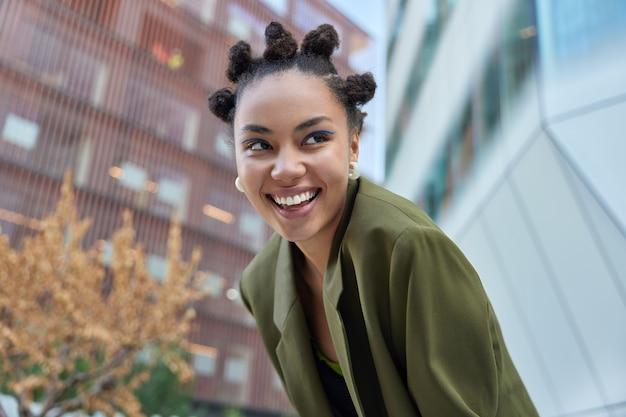 Meisje met knot kapsel lacht positief toont witte zelfs tanden gekleed in groene jas geconcentreerd weg poses tegen onscherpe achtergrond heeft plezier