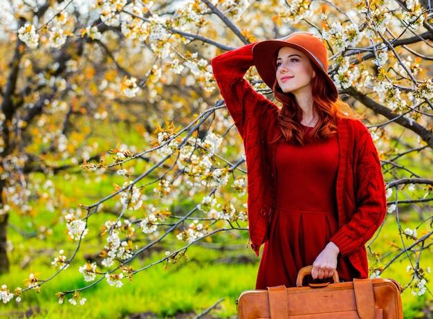 Meisje met koffer in de tuin van de bloesemkers