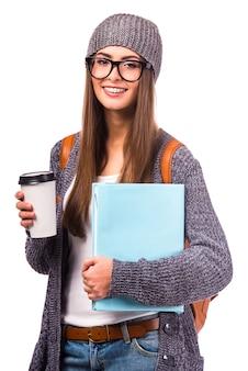 Meisje met koffie in de hand kijkt naar de voorkant.