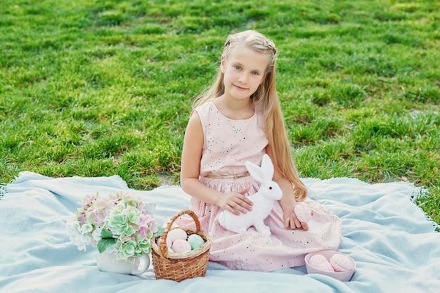 Meisje met konijn en eieren voor pasen in het park op groen gras