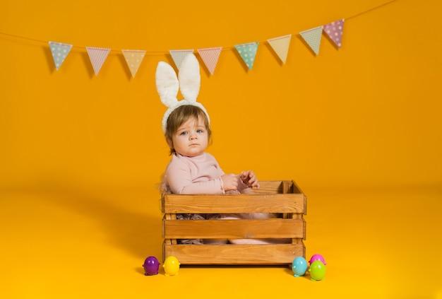 Meisje met konijnenoren zit in een houten doos met kleurrijke eieren op een gele achtergrond