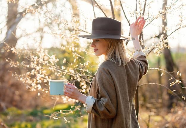 Meisje met kop van koffie in een tuin van de kersenbloesem bij zonsondergang