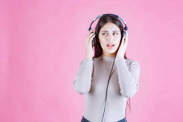 Meisje met koptelefoon die de muziek controleert en er serieus uitziet