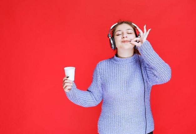 Meisje met koptelefoon die een koffiekopje vasthoudt en een teken van plezier toont.