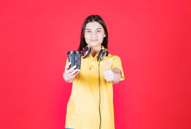 Meisje met koptelefoon die een zwarte wegwerpbeker vasthoudt en een positief handteken toont