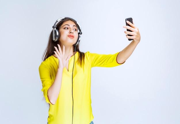 Meisje met koptelefoon die haar selfie neemt of een videogesprek voert.