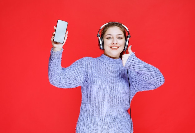 Meisje met koptelefoon die haar smartphone demonstreert en zich gelukkig voelt.