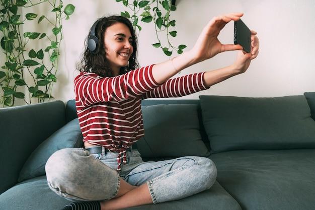 Meisje met koptelefoon die thuis een foto maakt met haar telefoon. technologie concept