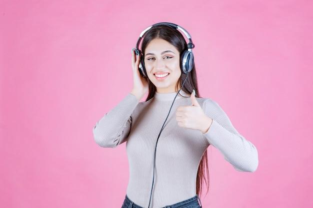 Meisje met koptelefoon luisteren naar de muziek en haar plezier tonen