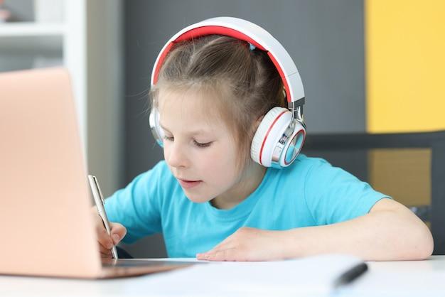 Meisje met koptelefoon maakt aantekeningen in notitieboekje op tafel is laptop