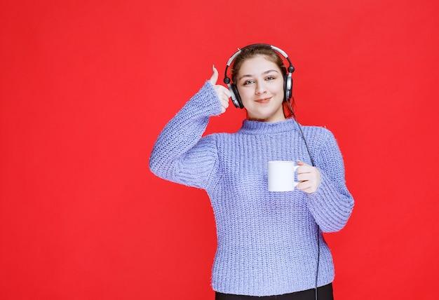 Meisje met koptelefoon met een koffiemok en glimlachen.