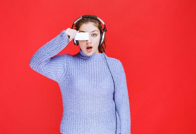 Meisje met koptelefoon met een visitekaartje en kijkt verrast.