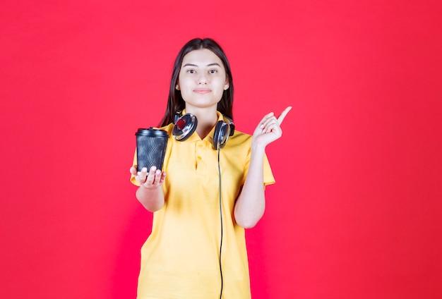 Meisje met koptelefoon met een zwarte wegwerpbeker drinken.
