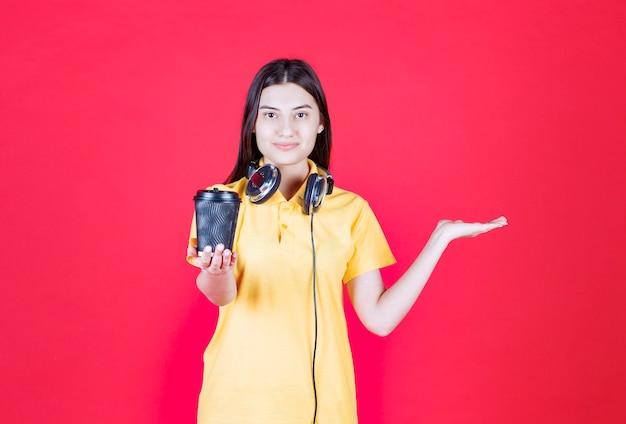 Meisje met koptelefoon met een zwarte wegwerpbeker met drank