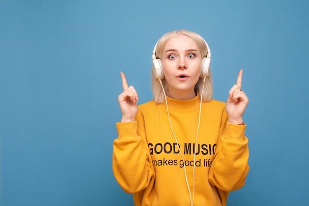 Meisje met koptelefoon op blauw, met een schokkend gezicht in de camera kijken en vingers op lege plaats tonen