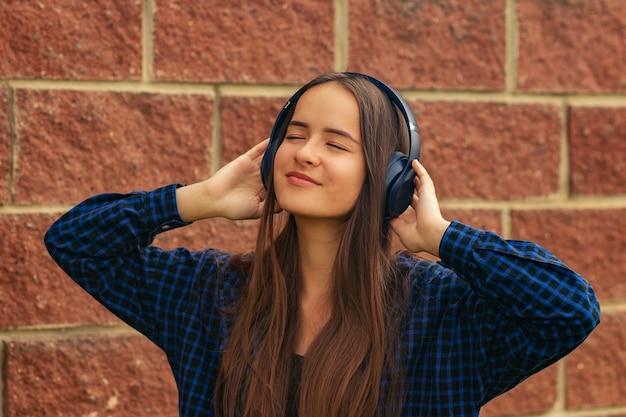 Meisje met koptelefoon op straat, dansen, genieten, naar muziek luisteren met haar ogen dicht