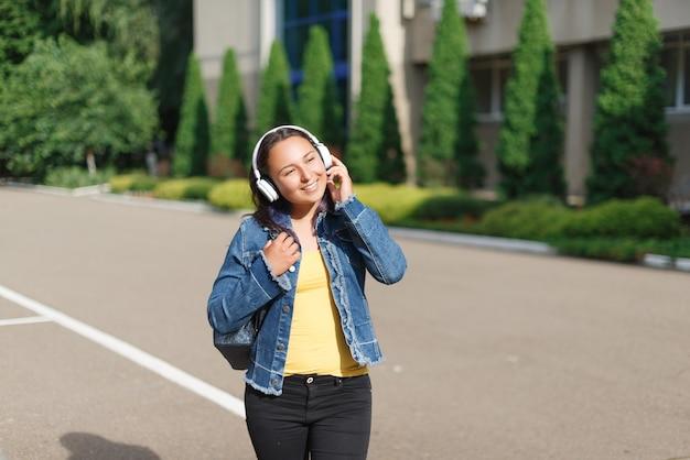 Meisje met koptelefoon wandelen in het park op een zonnige dag en luisteren naar muziek