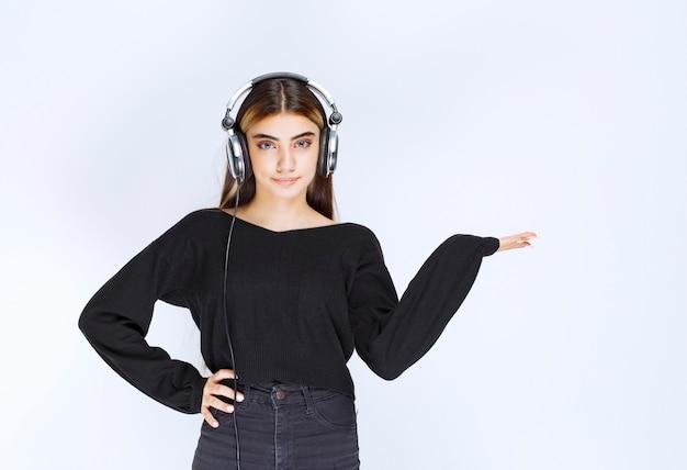 Meisje met koptelefoon wijzend op iets aan de rechterkant. hoge kwaliteit foto