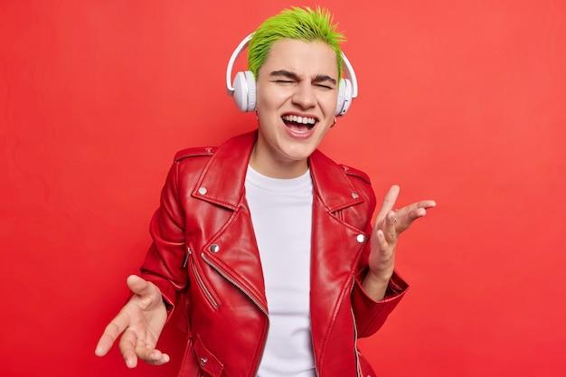 Meisje met kort groen haar zingt liedje mee veel plezier terwijl ze naar muziek luistert in een koptelefoon draagt een leren jas op rood