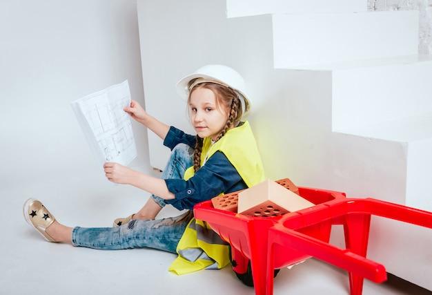 Meisje met kruiwagen op de witte muur. bouw