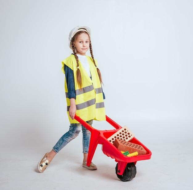 Meisje met kruiwagen op het witte landschap. bouw